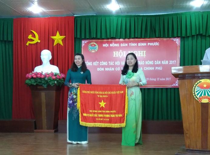 Đồng chí Lê Thị Xuân Trang, Ủy viên Ban Thường vụ Tỉnh ủy, Trưởng Ban Dân vận Tỉnh ủytrao Cờ thi đua của Chính phủ cho cho Hội Nông dân tỉnh Bình Phước